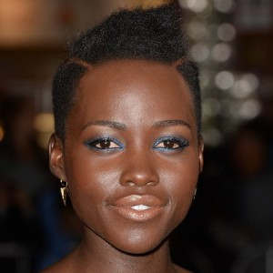 Lupita Nyongo rocking a peach matte lip and a strong blue liner.